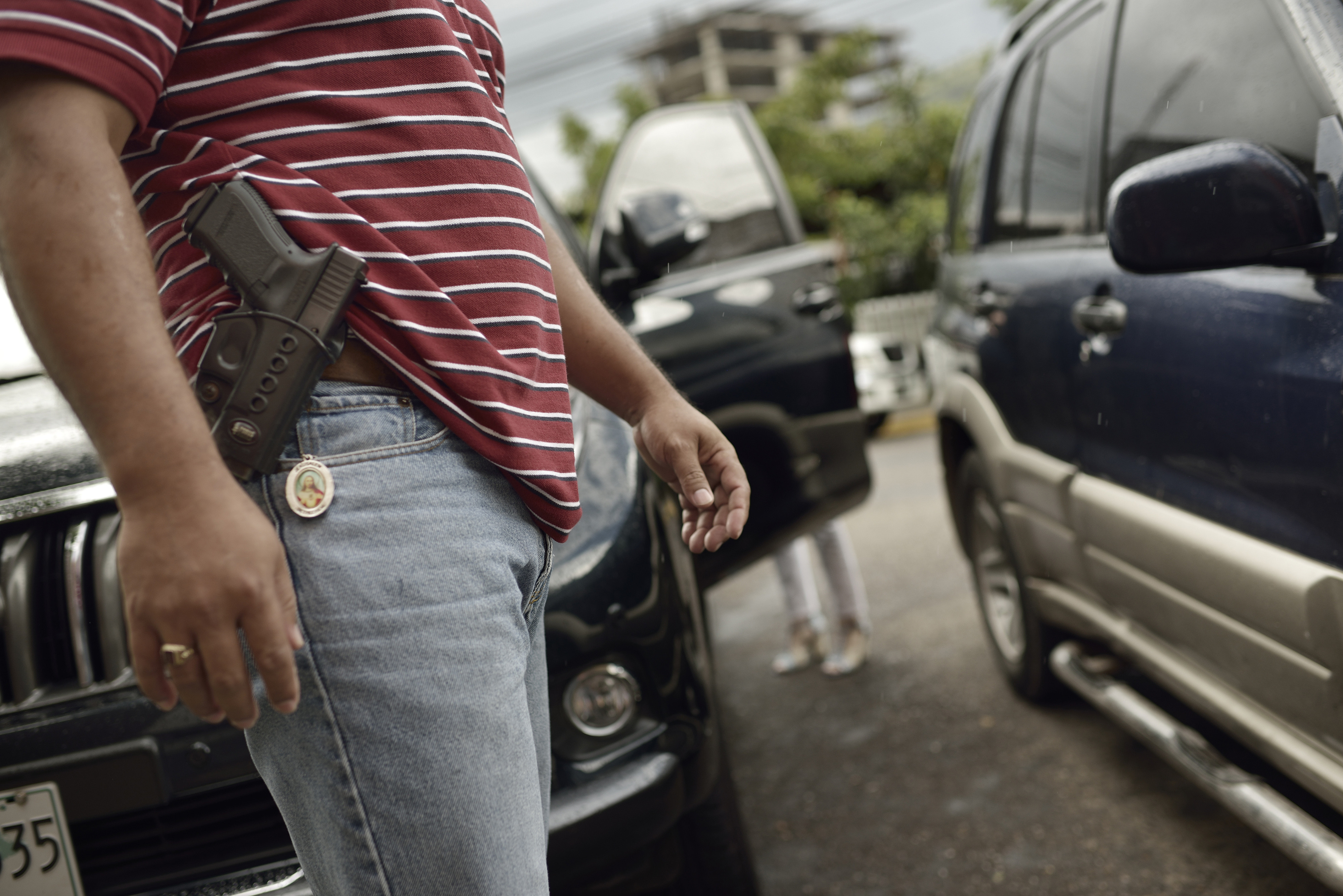 ©Kadir van Lohuizen / NOOR Caption: Honduras, Tegucigalpa, 2012, Private security guard watches a client entering the car. Many companies and residents of the city feel that the police is not to be trusted and hire private security companies. IG : @kadirvanlohuizen Twitter : @mediakadir